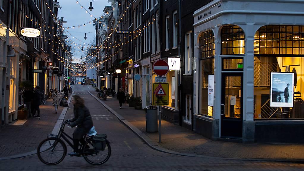Eine Frau fährt auf ihrem Fahrrad durch das ansonsten fast leere Einkaufsviertel der Neun Strassen in Amsterdam.