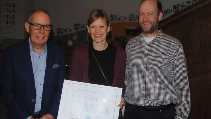 Kirchgemeindepräsident Martin Joss, Lisa Krebs (Reformierte Kirchen Bern-Jura-Solothurn) und Stefan Portmann (Oeme-Kommission) mit der Urkunde (von links).