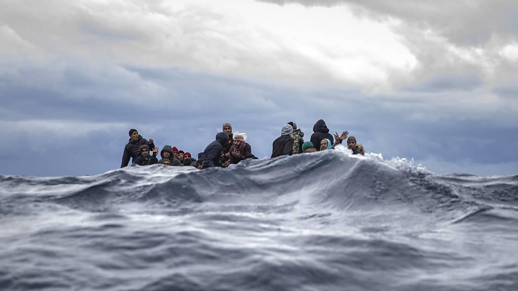 ARCHIV - Männer aus Marokko und Bangladesch sitzen in einem überfüllten Holzboot im Mittelmeer vor der Küste von Libyen. Foto: Santi Palacios/AP/dpa
