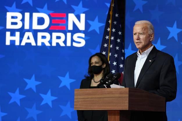 Joe Biden, zusammen mit Kamala Harris im Hintergrund.
