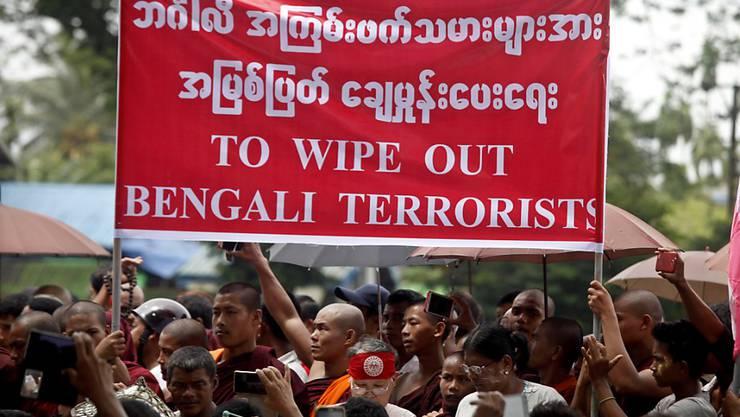Buddhistische Mönche tragen ein Transparent, auf dem zur Tötung von Rohingyas aufgerufen wird