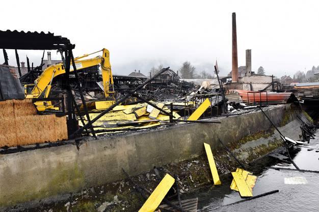 Ein Bagger war vor Ort, um das verkohlte oder teilweise noch glimmende Holz auseinander zunehmen. Dann wurde es von Feuerwehrmännern in Wasser getränkt.