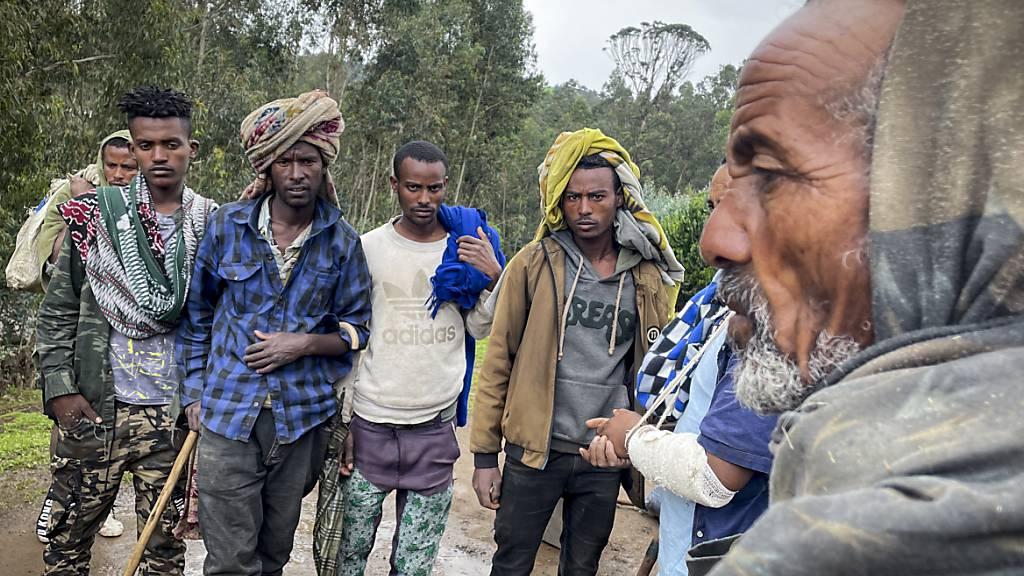 Männer versammeln sich, um mit dem am Arm verletzten Milizionär Kibret Bidere (2.v.r) in der Nähe des Dorfes in der Amhara-Region in Nordäthiopien zu sprechen. Foto: Uncredited/AP/dpa