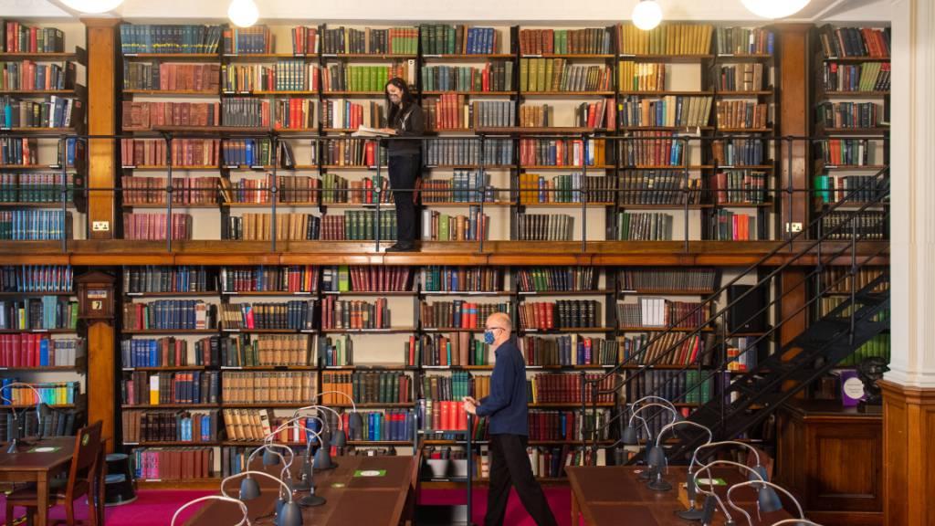 Ein Mitarbeiter ordnet Bücher in der London Library am St. James Square vor der geplanten Wiedereröffnung am 12. April. Foto: Dominic Lipinski/PA Wire/dpa
