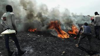Junge Männer verbrennen in Accra, der Hauptstadt von Ghana, Elektrogeräte, um an verwertbares Metall zu kommen.