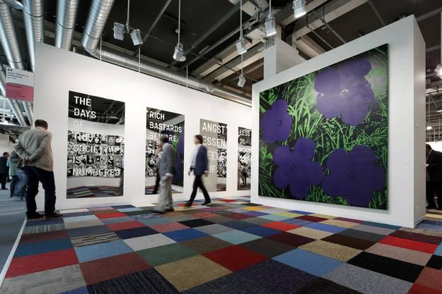 Hier knallts ganz schön bunt. Selbst der Boden bei Galvin Brown's Enterprise aus New York ist farbig kariert. Kunst oder Bodenleger? Wir tippten auf Kunst und lagen richtig. Den Boden entwarf Bildhauer Martin Creed. Falsch lagen wir dagegen beim Blumen-Warhol. Das Bild stammt von Warhol-Kopistin Sturtevant. Es kostet ein bisschen weniger, aber immerhin noch 600 000 Dollar.