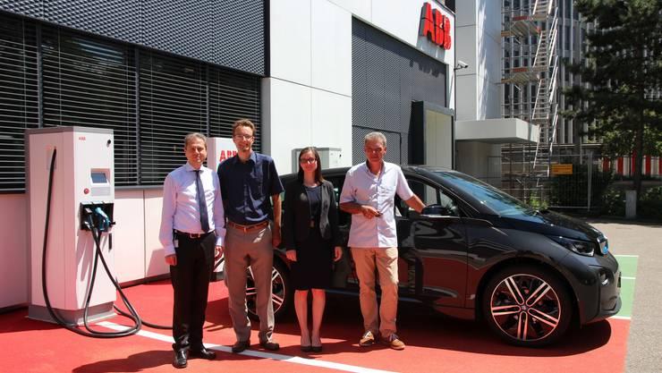 Von links: Remo Lütolf (ABB), Jonas Messmer (Hochschule Offenburg), Heike Stoll (Hochrheinkommission) mit dem Projektteilnehmer Hans-Peter Kimmig an der Elektrotankstelle in Baden.