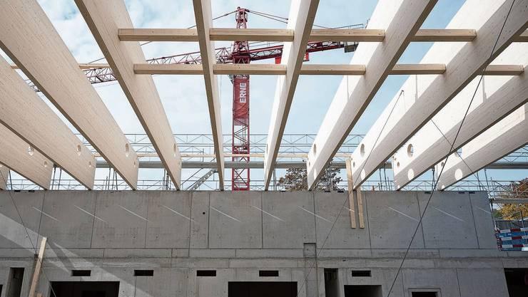 Die Dachbinder sind bereits montiert, weitere Holzelemente warten auf die präzise Einpassung.