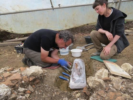 Mitarbeiter der Kantonsarchäologie bei der Bergung des Kurzschwertes aus einem Männergrab.