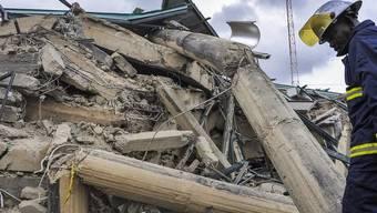 Ein Rettungshelfer vor den Trümmern des Einkaufszentrums
