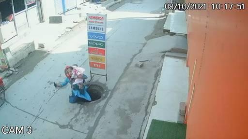 Frau mit Baby stürzt in offenen Abwasserschacht