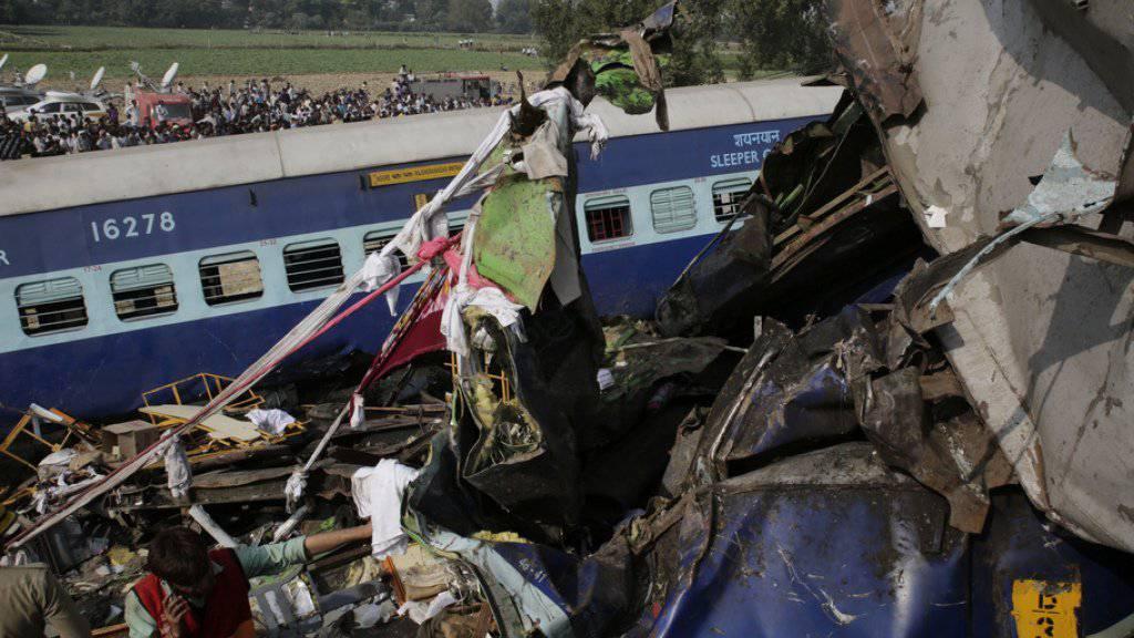 Rettungskräfte suchen in den völlig zerstörten Eisenbahnwagen nach Überlebenden. Beim Zugunglück in Indien kamen fast 100 Menschen ums Leben.