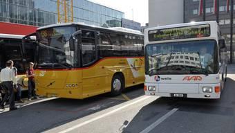 Ein gelber Postbus und ein weisser A-Welle-Bus der AAR stehen vor dem Bahnhof Aarau, 7. April 2010.
