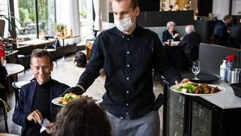 Servieren mit Mundschutz: Ein Kellner der «La Brasserie de Montbenon» bedient in Lausanne Gäste am ersten Tag der Wiedereröffnung.