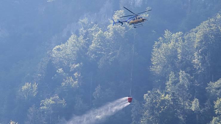 Ein Helikopter transportiert Löschwasser, um den Brandherd nach einem Kleinflugzeugabsturz am Lopper in Hergiswil im Kanton Nidwalden zu löschen.