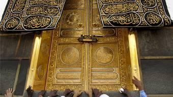 Gläubige berühren die goldene Tür der Kaaba in der Moschee von Mekka. Symbolbild.