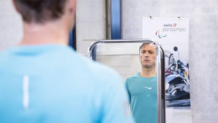 Paracycling-Fahrer Roger Bolliger mustert sich im Spiegel. Swiss Paralympic / Sabina Renfer