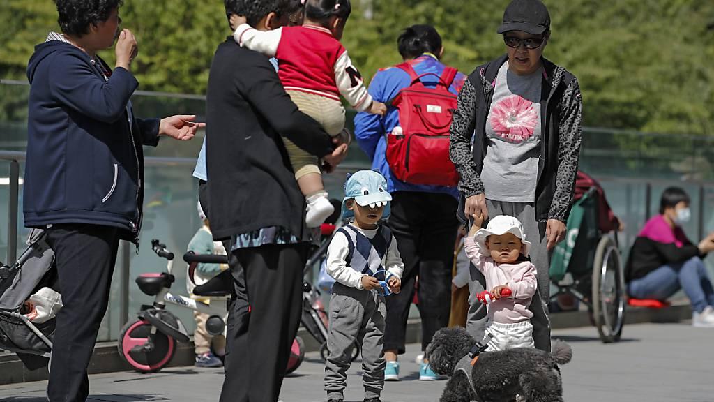 ARCHIV - Anwohner bringen ihre Kinder zum Spielen auf ein Gelände in der Nähe eines kommerziellen Bürogebäudes. China lockert seine Familienpolitik und erlaubt Paaren künftig drei Kinder. Foto: Andy Wong/AP/dpa Foto: Andy Wong/AP/dpa