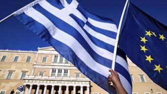 """Griechische und EU-Flagge vor dem griechischen Parlament in Athen. Griechenland möchte eine """"tragfähige Lösung, um in der Euro-Zone zu bleiben (Symbolbild)."""