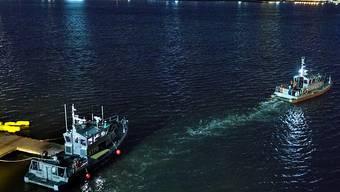 Polizeiboot bei dem über Wasser gehaltenen Helikopter im East River