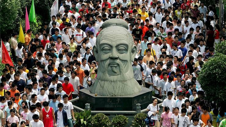 Studenten der Universität Wuhan laufen zu ihren Prüfungen an einer übergrossen Konfuzius-Büste vorbei.