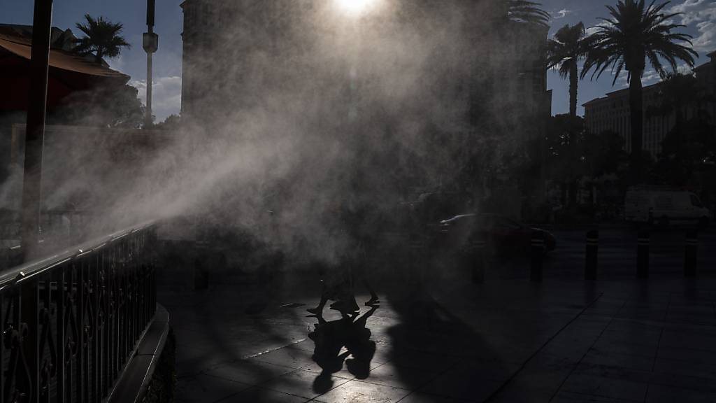 dpatopbilder - Menschen gehen in Las Vegas an Nebelmaschinen vorbei, die zur Abkühlung entlang des Las Vegas Strip eingesetzt werden. Las Vegas könnte an diesem Wochenende sein Temperatur-Allzeithoch erreichen, da für den Bundesstaat und große Teile der westlichen USA extreme Hitze vorhergesagt wird. Foto: John Locher/AP/dpa