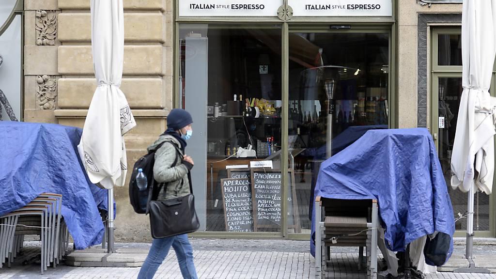 Tische und Stühle eines Restaurants sind unter einer Schutzhülle zusammengestellt. Tschechien greift aufgrund steigender Corona-Zahlen zu drastischen Maßnahmen, die einem landesweiten Lockdown gleichkommen. Foto: Kateøina ?ulová/CTK/dpa