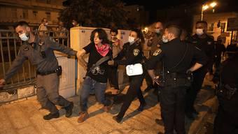 Israelische Polizisten führen einen Demonstranten bei einer Demonstration gegen Israels Ministerpräsidenten Netanjahu in der Nähe der Residenz des Ministerpräsidenten ab. Foto: Sebastian Scheiner/AP/dpa