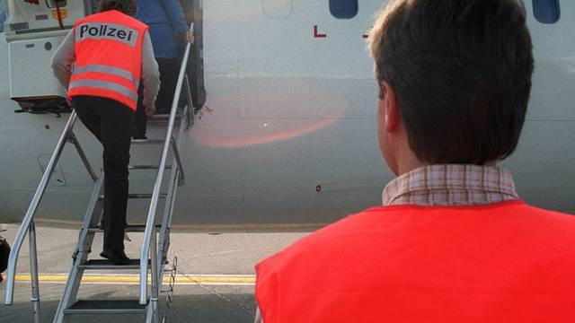 Polizisten begleiten jemanden zur Ausschaffung ins Flugzeug (Symbolbild)