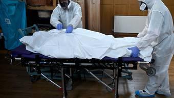 Bestatter in London kümmern sich in Schutzkleidern um ein Corona-Todesopfer.