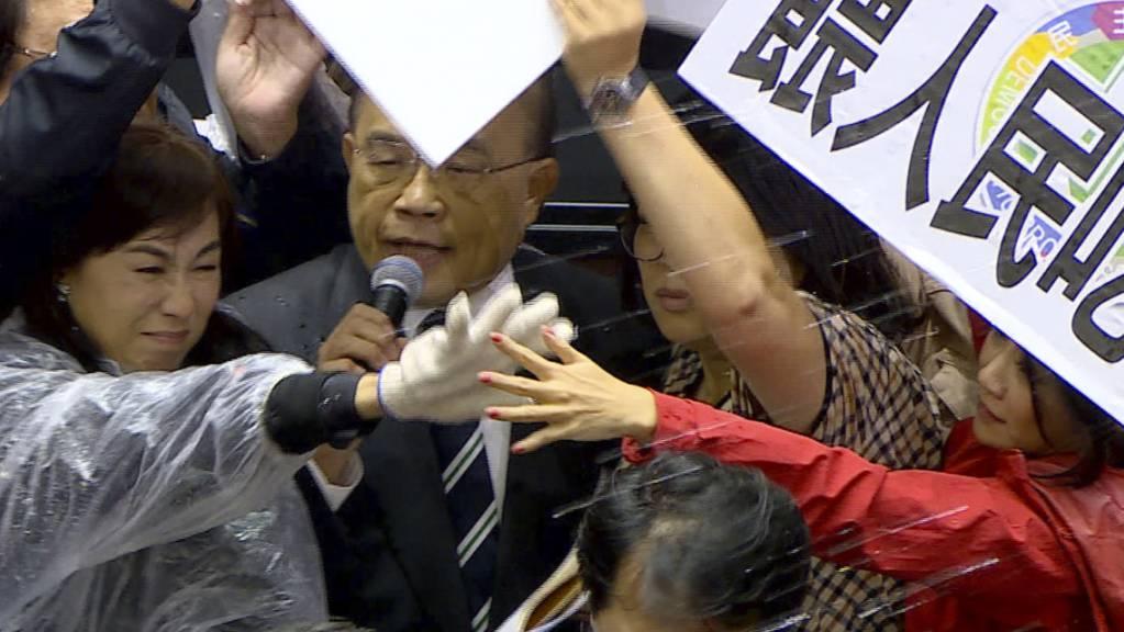 SCREENSHOT - Ministerpräsident Su Tseng-chang wird im Parlament mit Schweineinnereien beworfen. Foto: -/FTV/AP/dpa