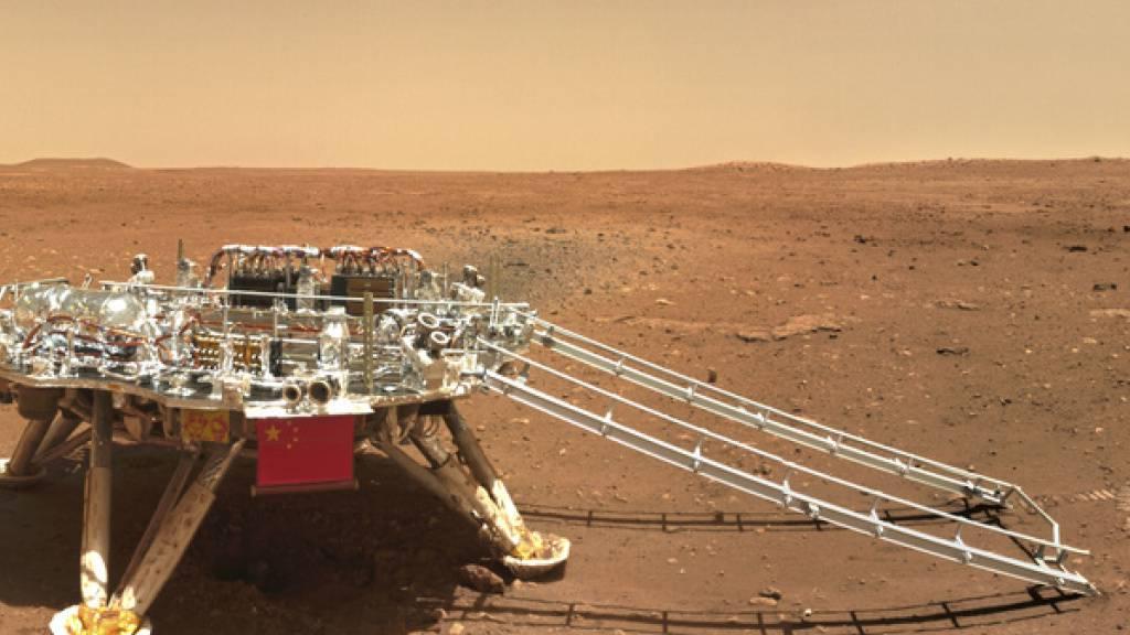 Auf dem Foto der China National Space Administration (CNSA) vom Freitag ist rechts von der Landeplattform deutlich die Spur zu sehen, welche der Rover Zhurong beim Wenden im Marssand gelegt hat. China freut sich, einen sichtbaren Eindruck auf dem Roten Planeten hinterlassen zu haben.
