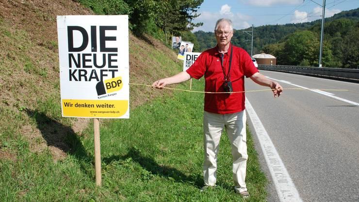 Viel zu nahe an der Strasse: Bruno Bühler misst den Abstand eines BDP-Plakats in Rudolfstetten. fh