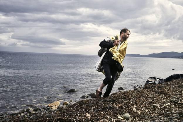 Wie aus dem Meer entstiegen, verlässt ein syrischer Flüchtling den Strand von Lesbos und geht, eingehüllt in eine Thermodecke, hoffnungsvoll Europa entgegen.