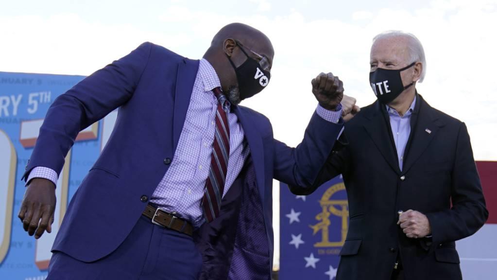 dpatopbilder - Joe Biden (r), gewählter Präsident (President-elect) der USA, steht während einer Wahlkampfveranstaltung neben dem Raphael Warnock, demokratischer Kandidat für den US-Senat, auf der Bühne. Foto: Carolyn Kaster/AP/dpa
