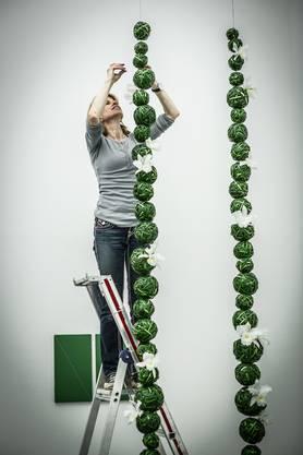 Priska Isenschmid hängt Kugeln aus Liliengras vor ein grün-weisses Werk von John Armleder.