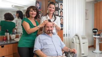 Antonia De Simone-Secreti (links) und Pina Corso-Secreti kümmern sich im Coiffeursalon Leonardo um die Haare ihres Vaters, der es sichtlich geniesst. Mario Heller