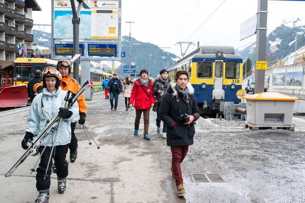 Einige Touristen kommen am Bahnhof an.