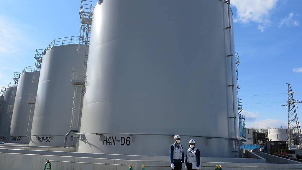 ARCHIV - Zwei Mitarbeiter des Betreiberkonzerns Tepco stehen vor riesigen Tanks, in denen verstrahltes Wasser, das bei der andauernden Kühlung der beschädigten Reaktoren von Fukushima anfällt, gelagert wird. Foto: Lars Nicolaysen/dpa