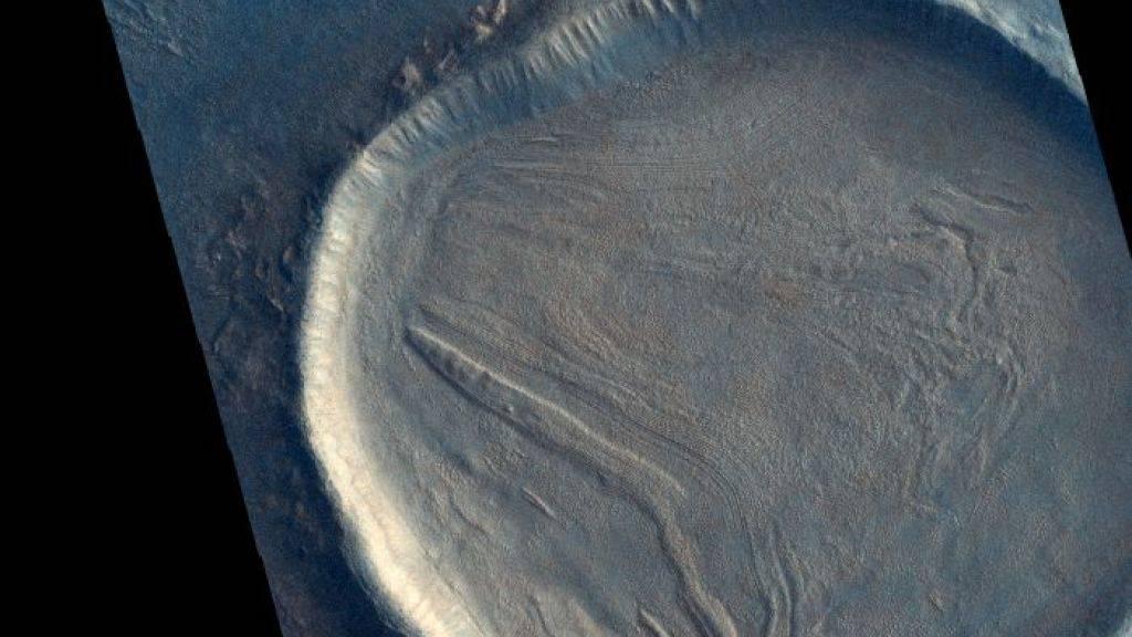 """Dieser unbenannte Krater auf dem Mars ist mit Material gefüllt, das """"faltig"""" aussieht. Dies deutet darauf hin, dass das Material einmal hierhin geflossen ist und wahrscheinlich eine Mischung aus Gestein, Eis oder Frost und anderen Bodenablagerungen beinhaltet."""