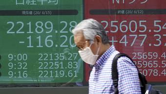 Ein Mann, der wegen der Corona-Pandemie einen Mundschutz trägt, geht an einer elektronischen Anzeigetafel vorbei, welche den japanischen Nikkei 225-Index und den New Yorker Dow-Index anzeigt. Foto: Eugene Hoshiko/AP/dpa