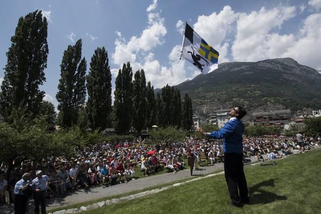 Flaggenwurf vor der Zuschauerschaar an der Eröffnungszeremonie.