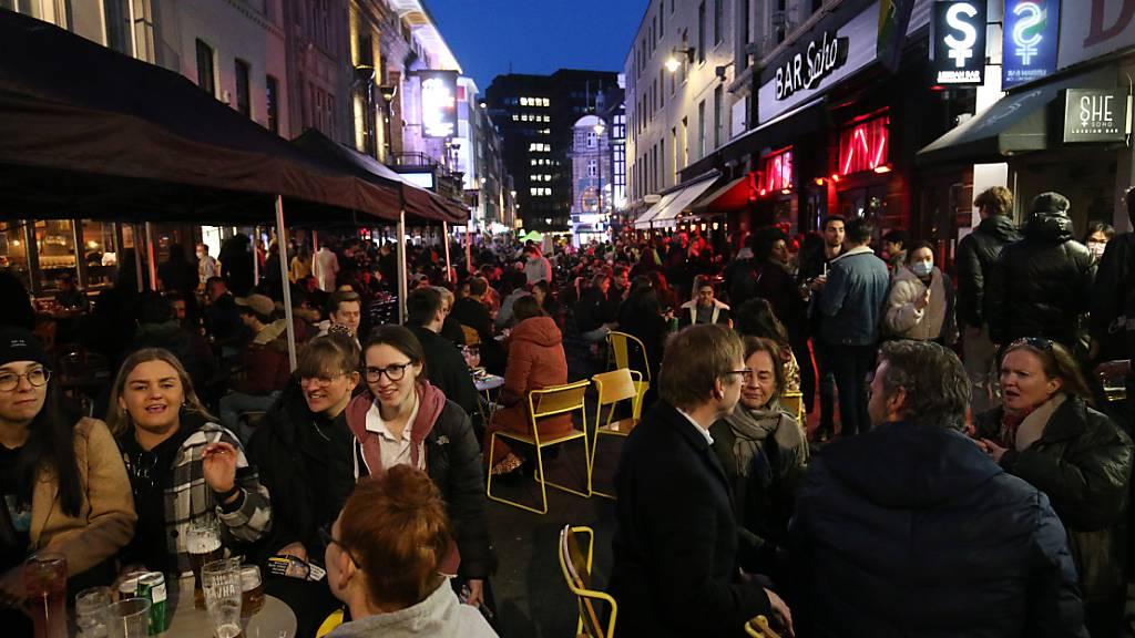 Menschen versammeln sich für Getränke und Essen in der Old Compton Street, Soho, im Zentrum Londons. Die britische Regierung lässt dank fortschreitender Corona-Impfungen und sinkender Fallzahlen in Großbritannien etwas die Zügel locker. Foto: Jonathan Brady/PA Wire/dpa