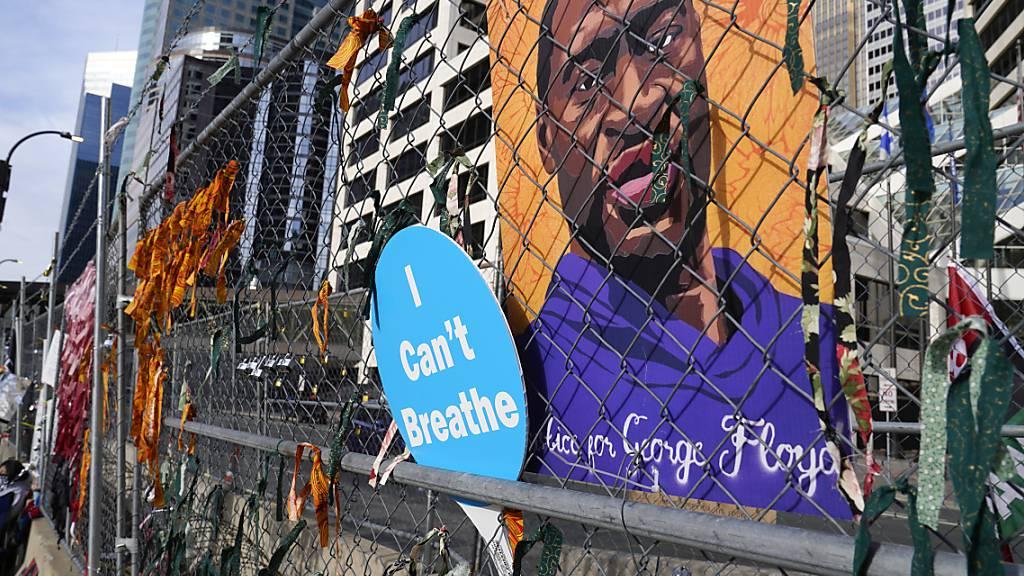 ARCHIV - Ein Plakat mit einem Bild von George Floyd hängt an dem Zaun vor einem Regierungsgebäude von Hennepin County in Minneapolis. Foto: Jim Mone/AP/dpa