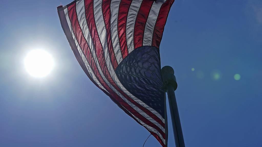 ARCHIV - Eine US-Flagge weht  mit der Sonne im Hintergrund in der Innenstadt von Seattle. Foto: Ted S. Warren/AP/dpa