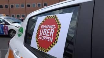 Basel 28.6.16. - «Stopp Uber-Dumping». Taxifahrer in Basel machen zum zweiten Mal eine Demonstration. Verlangt wird ein Verbot von UBER. Der US-Amerikanische Internetdienst, der Fahrer via App vermittelt, müsse verboten werden. Dieses Verbot solle so lange gelten, bis sich das Unternehmen an Schweizer Gesetze halte.
