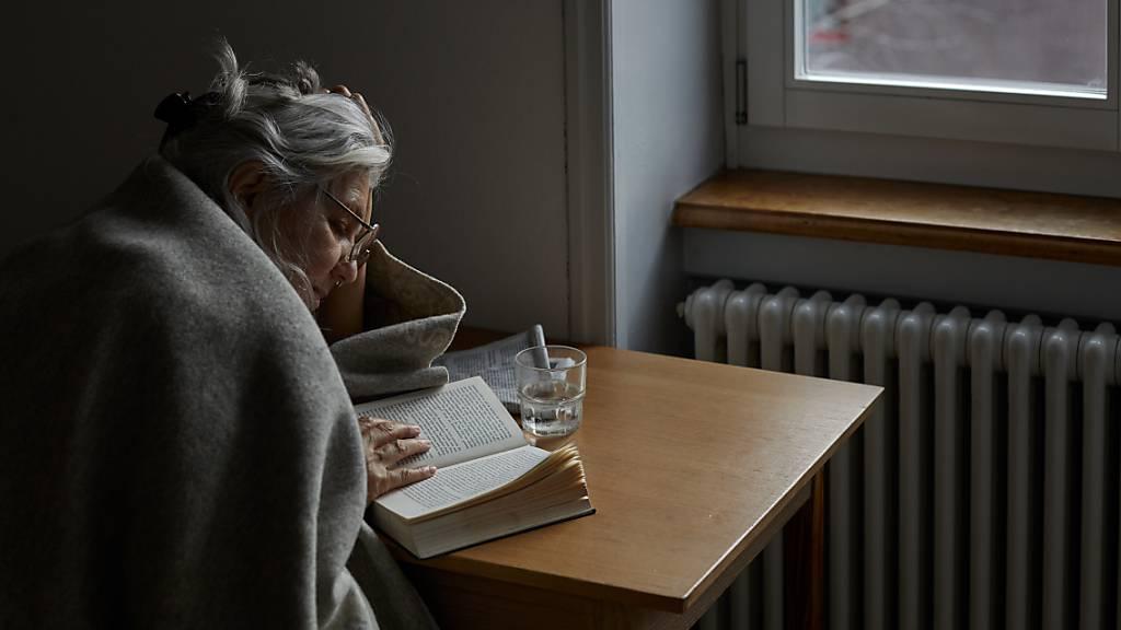 Armut hat viele Gesichter: Eine ältere Frau beim Lesen. (Gestelltes Symbolbild)