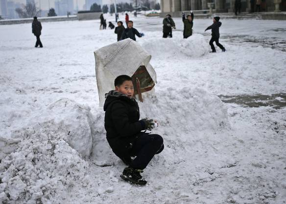 A North Korean boy takes cover during a snowball fight on Kim Il Sung Square in Pyongyang, North Korea, where the winter season has started, on Sunday, Dec. 16, 2018. (AP Photo/Dita Alangkara)