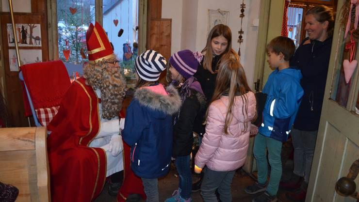 Die Kinder besuchen den Samichlaus in seinem feierlich geschmückten «Hüsli» an der Holzgasse in Hausen;Kinder und Erwachsenen stehen Schlange, um mit dem Samichlaus zu sprechen.