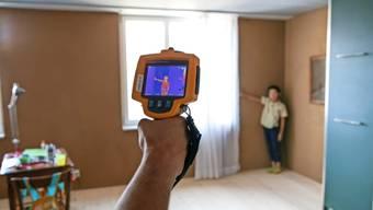 Kontrolle mit der Wärmebildkamera: Die Farbe zeigt an, wie stark die ockerfarbene Lehmwand in der Wohnung kühlt.